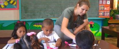 Voluntaria social enseñándole los colores a niños en Filipinas.